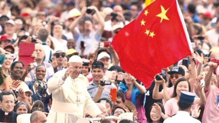 Pope Francis waves to the crowd as he passes a person holding a Chinese flag during his weekly general audience in St.Peter's Square.