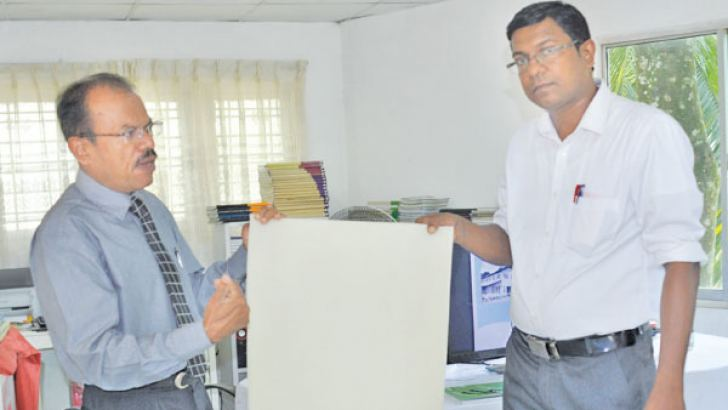 Superintendent Atale Estate Lakshman Amaratunga with factory officer Upul Gunaratne displaying a Latex Pale Crape sheet Workers at the factory