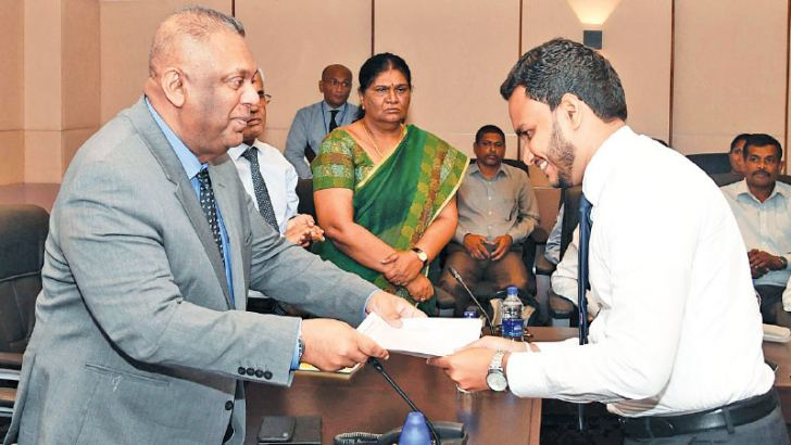 Minister Mangala Samaraweera presents an appointment letter to a new recruit.
