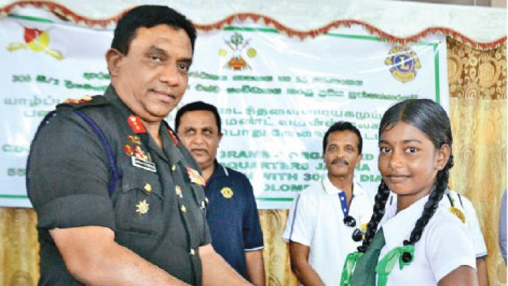 Jaffna Commander Major General Darshana Hettiarrachchi presents stationery to a student.