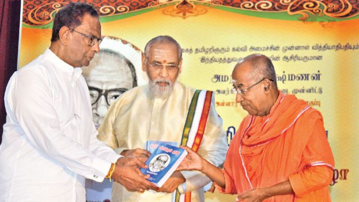 Minister D. M. Swaminathan handing over the first copy to Chief Minister C. V.  Wigneswaran.