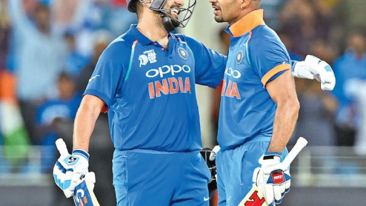 India's Rohit Sharma and Shikhar Dhawan greet each other during their double century opening partnership against Pakistan in the Asia Cup Super Four match played at Dubai International Cricket Stadium on Sunday. - AFP