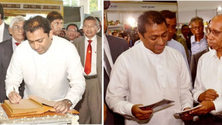 Education Minister Akila Viraj Kariyawasam making a note in the souvenir. Looking on are (from the left), Gill Caldicott, Vijitha Yapa and H D Premasiri. Pictures by Sarath Peiris