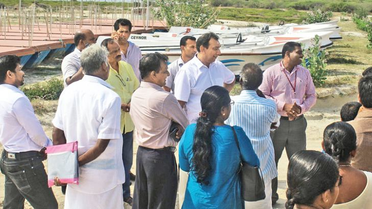 Minister Aluvihare inspects the goods along with other officials.