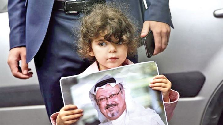 A girl holds a poster with a photo of missing Saudi writer Jamal Khashoggi during a protest.