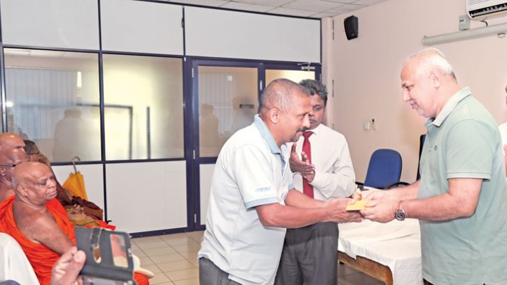 Minister Rauff Hakeem presents a donation to a representative from a community-based organisation in the Kandy district.