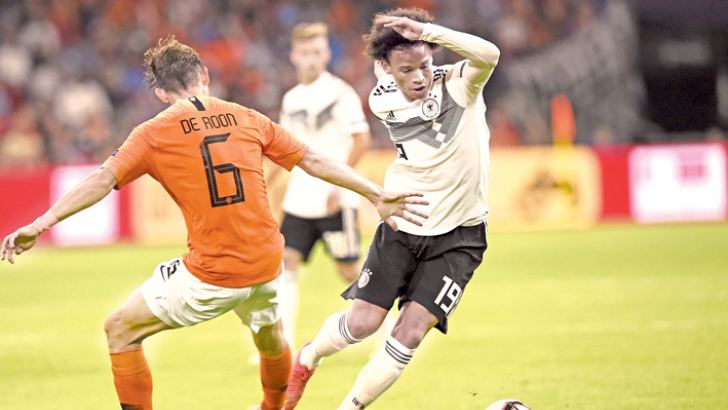 Netherlands' midfielder Marten de Roon (L) vies with Germany's midfielder Leroy Sane during the UEFA Nations League football match between Netherlands and Germany, on October 13, 2018 at Johan Crujiff ArenA in Amsterdam. AFP