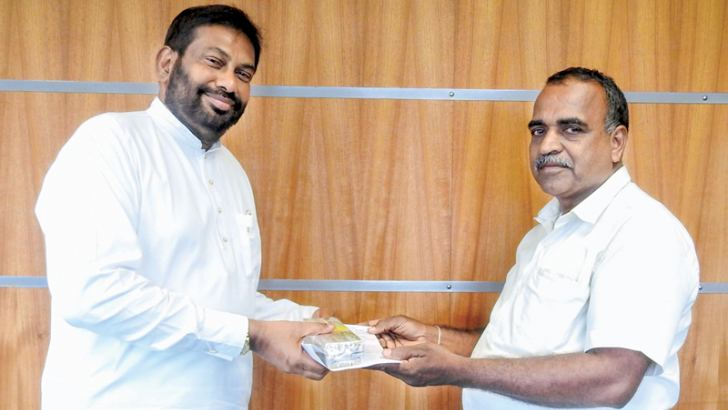 K. Wickramarachchi presents his invention to Minister Daya Gamage.