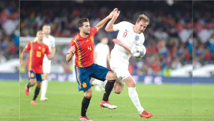 England's forward Harry Kane (R) vies for the ball with Spain's defender Nacho (L) during the UEFA Nations League football match between Spain and England on October 15. AFP