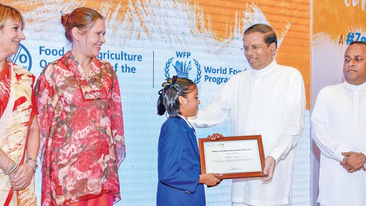 President Maithripala Sirisena presents a certificate to a schoolgirl at celebrations to mark World Food Day on Tuesday. Picture courtesy President's Media Division