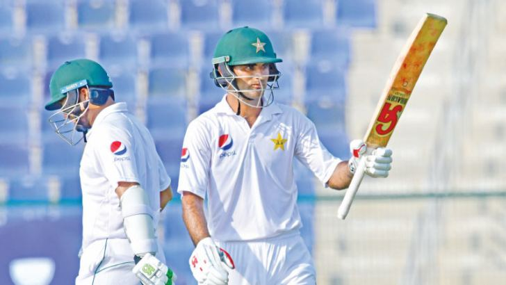 Pakistani cricketer Fakhar Zaman (R) celebrates his half century (50 runs) during day two of the second Test cricket match in the series between Australia and Pakistan at the Abu Dhabi Cricket Stadium in Abu Dhabi on October 17. AFP