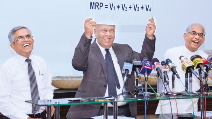 Finance and Mass Minister Media Mangala Samaraweera showing the much awaited fuel pricing formula at a media conference held at the Finance Ministry yesterday. State Minister Eran Wickremaratne and Finance Ministry Secretary Dr. R.H.S. Samaratunga look on. Picture by Hirantha Gunathilake