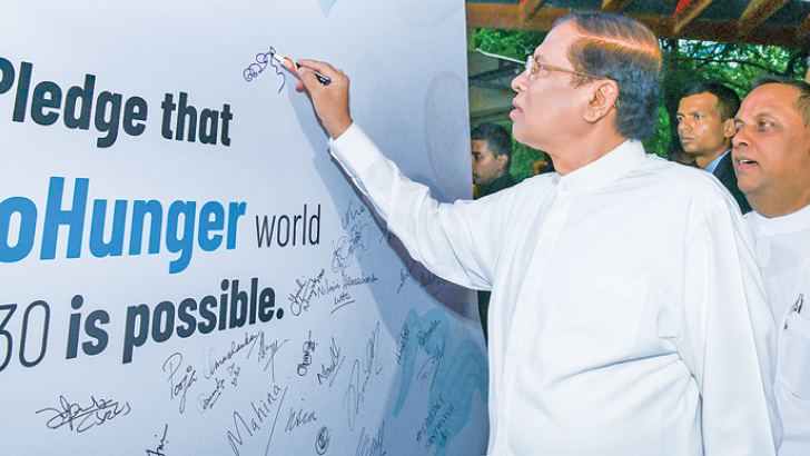 President Maithripala Sirisena signs the pledge to work for zero hunger, at World Food Day celebrations in Colombo, on Tuesday.