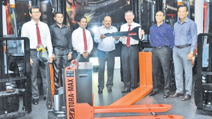 Managing Director of Toyota Lanka Shungo Yoshioka hands the keys to Lion Brewery dealers.