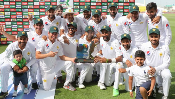 The Pakistan team celebrates with the trophy at the end of day four of the second Test cricket match between Australia and Pakistan at Sheikh Zayed stadium in Abu Dhabi on October 19. AFP