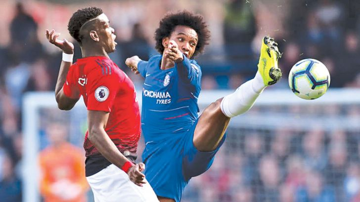 Manchester United's Paul Pogba in action with Chelsea's Willian.
