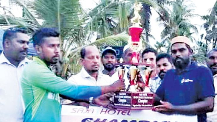 The skipper of Addalaichenai New Star Sports Club receiving the trophy.