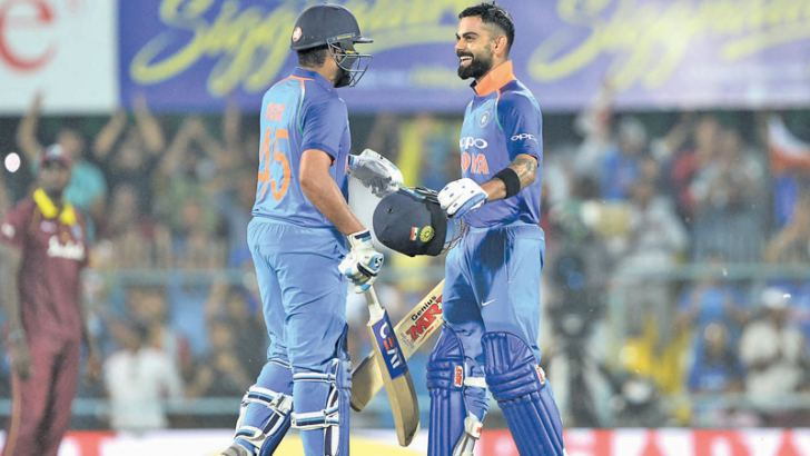 Indian batsman and team captain Virat Kohli (R) celebrates with his teammate Rohit Sharma after completing his century (100 runs) during the first one day international (ODI) cricket match between India and West Indies at Barsapara Cricket Stadium in Guwahati on October 21. AFP