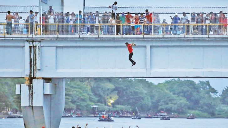 A migrant from Guatemala jumps off a bridge to enter Ciudad Hidalgo, Mexico.