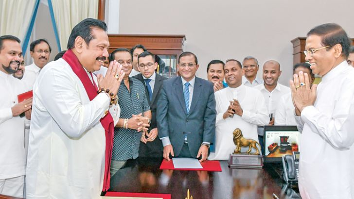 Former President Mahinda Rajapaksa sworn in as the new Prime Minister before President Maithripala Sirisena at the Presidential Secretariat Friday. Picture by Chandana Perera