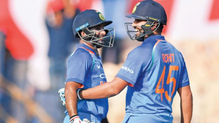 India cricketer Rohit Sharma (R) celebrates with teammate Ambati Rayudu after scoring a century during the fourth one day international (ODI) cricket match against West Indies at the Brabourne Stadium in Mumbai on Monday.  - AFP