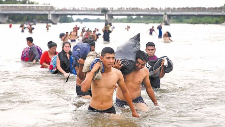 Central American migrants, part of a caravan trying to reach the US cross the Suchiate River to avoid the border checkpoint in Ciudad Hidalgo, Mexico on Monday.