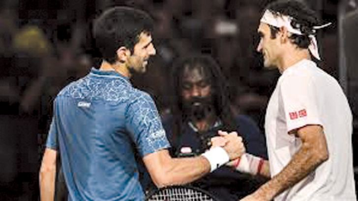Serbia's Novak Djokovic (L) and Switzerland's Roger Federer shake hands at the end of their men's singles semi-final tennis match on day six of the ATP World Tour Masters 1000 - Rolex Paris Masters - indoor tennis tournament at The AccorHotels Arena in Paris, on Saturday. - AFP