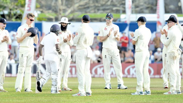 England cricketers applaud Rangana Herath as he comes to bat in his final Test match. – AFP