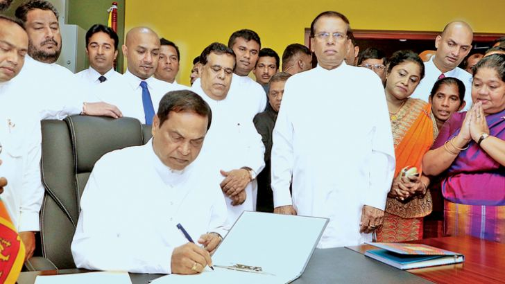 President Maithripala Sirisena looks on as State Minister of Women and Child Affairs Piyasena Gamage assumes duties at his Ministry yesterday. Picture by Saman Sri Wedage