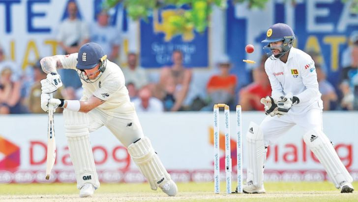 England cricketer Ben Stokes loses his off bail as he is bowled by Dilruwan Perera for 62 watched by wicket-keeper Niroshan Dickwella. – AFP