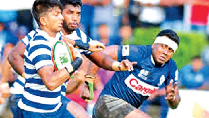 A Navy SC player makes a break hotly pursued by a Police player in the dialog 'A' Division inter-club league rugby match played at Police park yesterday.
