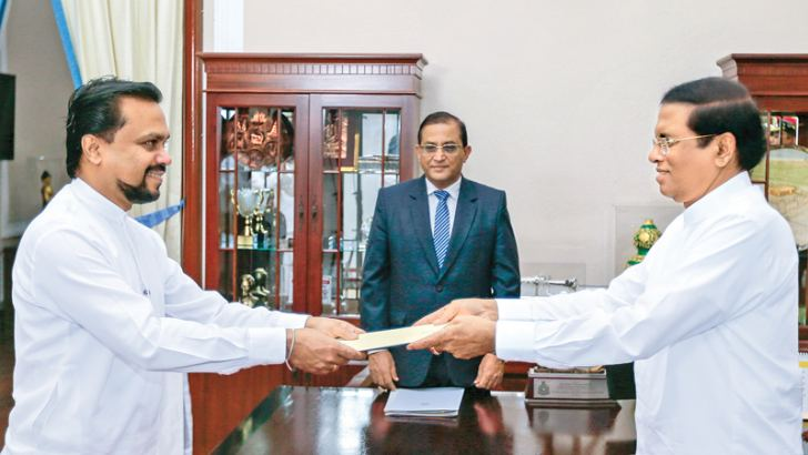 Parliamentarian Wimal Weeawansa was sworn in as Minister of Housing and Social Welfare before President Maithripala Sirisena at the Presidential Secretariat yesterday . Secretary to the President Udaya R Seneviratne was also present. Picture by Nissanka De Silva