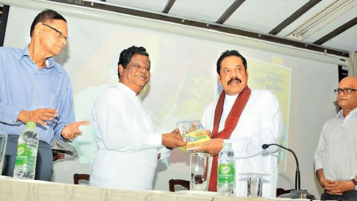 Minister Bandula Gunawardane presenting the first copy of the book to Prime Minister Mahinda Rajapaksa. Picture by Sudath Malaweera