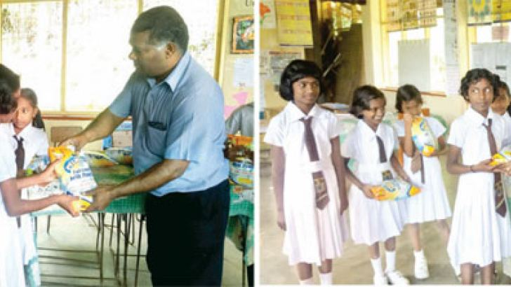 USCOD Centre representatives handing over Pelwatte milk powder to the students.