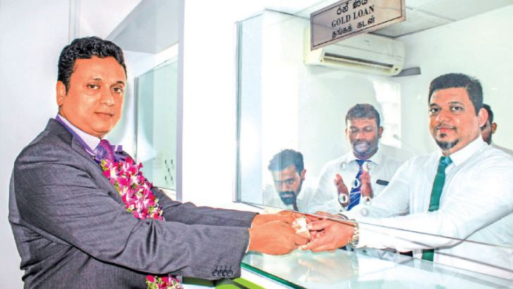CEO Kanrich Finance Shiran Weerasinghe making the first transaction at thr pawning counter st the  Ambalangoda branch.