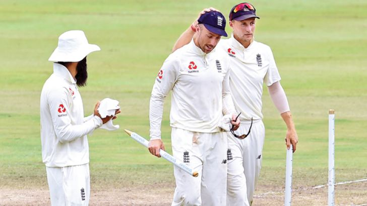 England's captain Joe Root (R) walks back to the pavilion with teammates Jack Leach (C) and Moeen Ali after they won the second Test match against Sri Lanka by 57 runs at the Pallekele International Cricket Stadium yesterday to take a winning 2-0 lead in the three-match series.  AFP