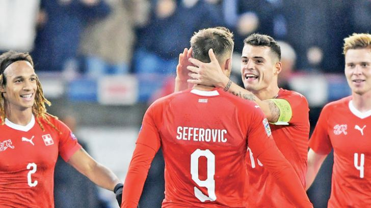 Forward Haris Seferovic (C) celebrates with teammates after scoring his third goal to end Belgium's hopes in the 84th minute. AFP