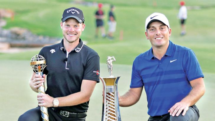 Danny Willett of England (L) poses with the DP World Tour trophy next to Francesco Molinari of Italy and his Race to Dubai trophy on November 18. AFP