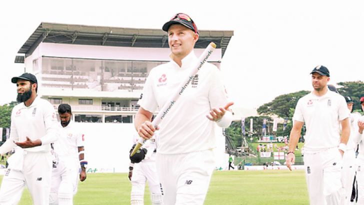 Joe Root the England captain with a wicket as souvenir leads his team to the pavilion after their victory in the second Test against Sri Lanka at Pallekele which gave them a winning 2-0 lead in the three-match series.