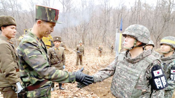 "A South Korean soldier and his North Korean counterpart taking part in the ""recent"" roadworks shaking hands with their colleagues watching."