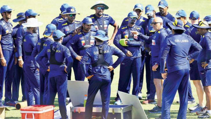 Coach Chandika Hathurusingha has a chat with Sri Lanka cricketers at practice as they try to avoid a 3-0 whitewash against England in the third and final Test starting at the SSC grounds on Friday. – AFP