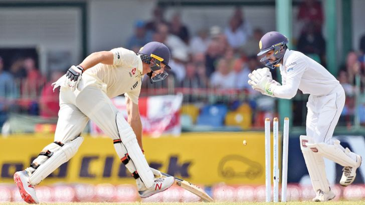 England's Jos Buttler is stumped by Sri Lanka wicket-keeper Niroshan Dickwella for 64 on the third day of the third and final Test at the SSC grounds yesterday. AFP