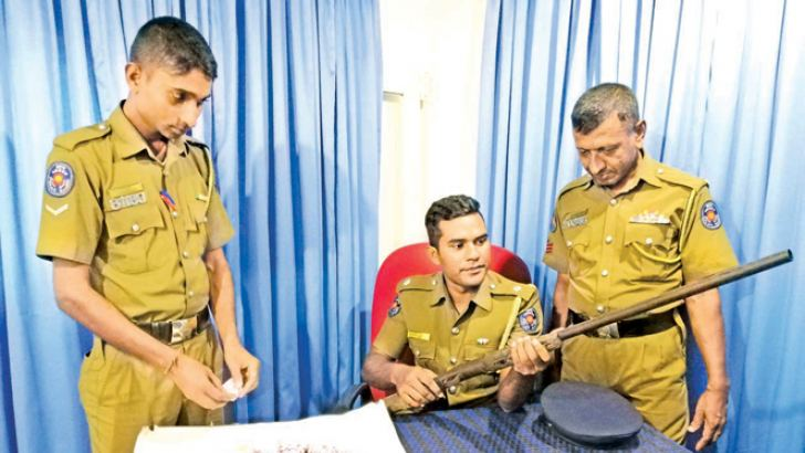 Uppuveli Police display the gun and packets of gunpowder that they seized from the suspect.