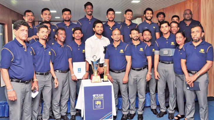 Deaf winning team players and officials pose for a photograph with Sri Lanka captain Dinesh Chandimal and Roshen Silva.