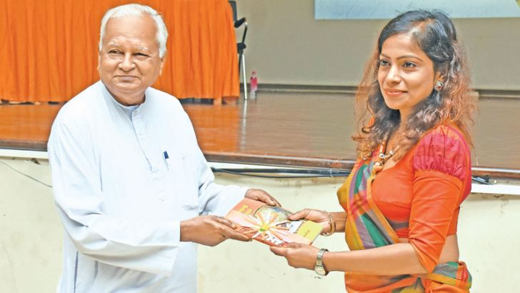 Sakunthala Seneviratne handing over a copy of her book to Siri sumana Godage.  Picture by W.P. Darmasena, Matara Group Corr.
