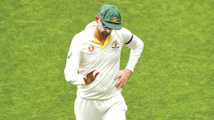 Australian cricketer Nathan Lyon wearing black arm band.