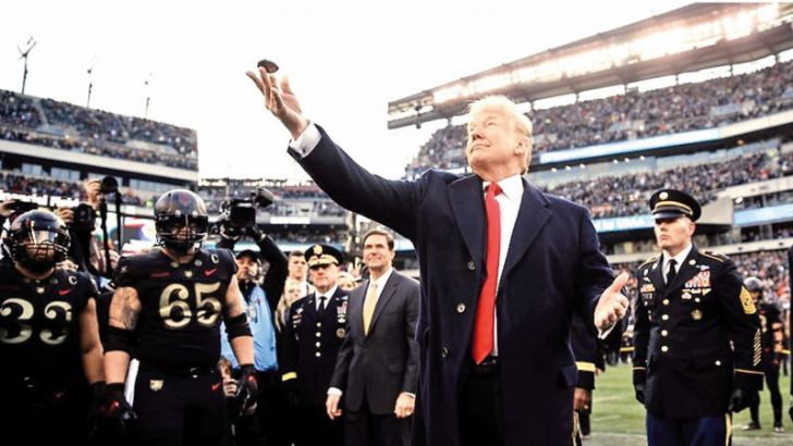 US President Donald Trump tosses the coin ahead of an NCAA college football between Army and Navy,  in Philadelphia on Saturday.