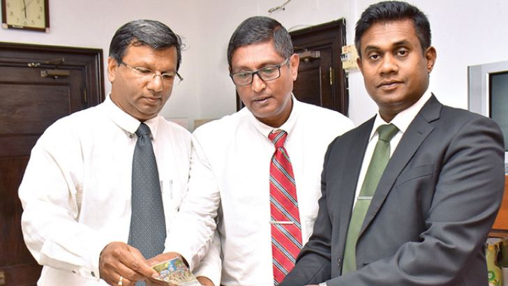 ANCL Director Editorial Dinesh Dodangoda (right) hands over the draw of coupon 2 to Deputy General Managers Subash Karunaratne (centre) and Narada Sumanaratne (left). Picture by Sudharshana Mayadunne
