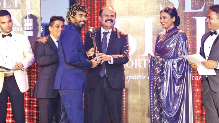 Lasith Malinga receiving the Most Popular Sports Personalty award from the SLT Chairman Kumarasinghe Sirisena during the SILK sports awards ceremony at the BMICH recently. Also in the picture, Head of the Jury panel  Harsha Abeykoon, sportsinfo.com Chairman Tilan Rangana and its Managing Director Nilakshi Ratnasinghe.