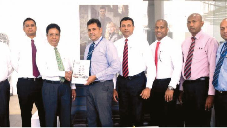 Sanjay Wijeymanne Deputy General Manager of HNB Retail Banking exchanging the agreement with Sujith Peiris Director of Strategic Business Development at Hyundai Lanka Flanked by Hyundai officials and HNB Bank officials.